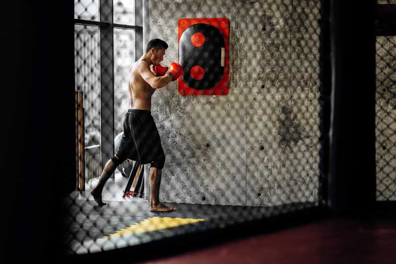 Sportsman with a naked torso and in the red boxing gloves hits equipment for boxing on a concrete wall in the gym behind the net
